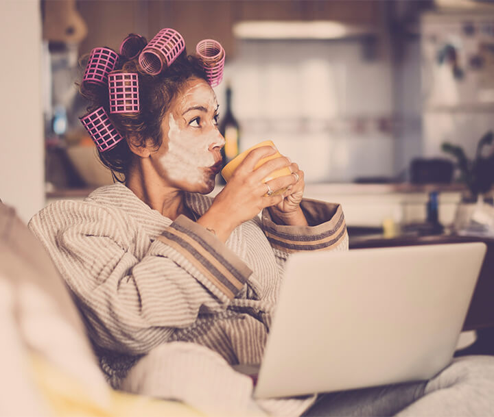 Woman sitting on a sofa in curlers drinking tea and looking at a laptop